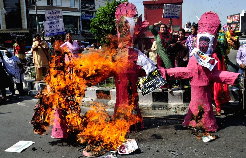 Congress activists burn the effigies of Prime Minister Narendra Modi, Finance Minister Arun Jaitley and Petroleum Minister Dharmendra Pradhan during a demonstration against price hike in ... - Narendra Modi and Arun Jaitley
