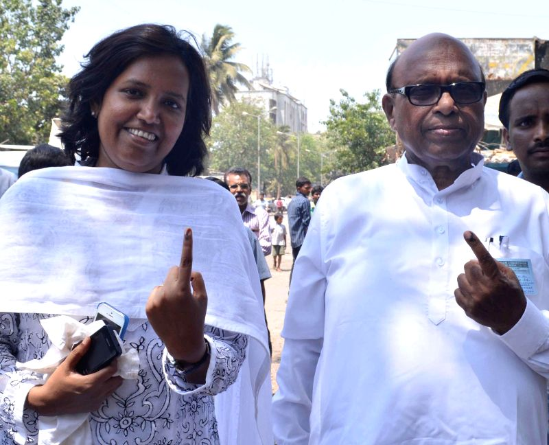 Congress candidate for upcoming 2014 Lok Sabha Election from South Central Mumbai Eknath Gaikwad shows his fore finger marked with phosphorous ink after casting his vote at a polling booth during the