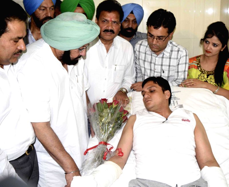 Congress leader Captain Amarinder Singh meets advocate Vaneet Mahajan who is admitted in the hospital after being fatally attacked in Amritsar on May 15, 2014.
