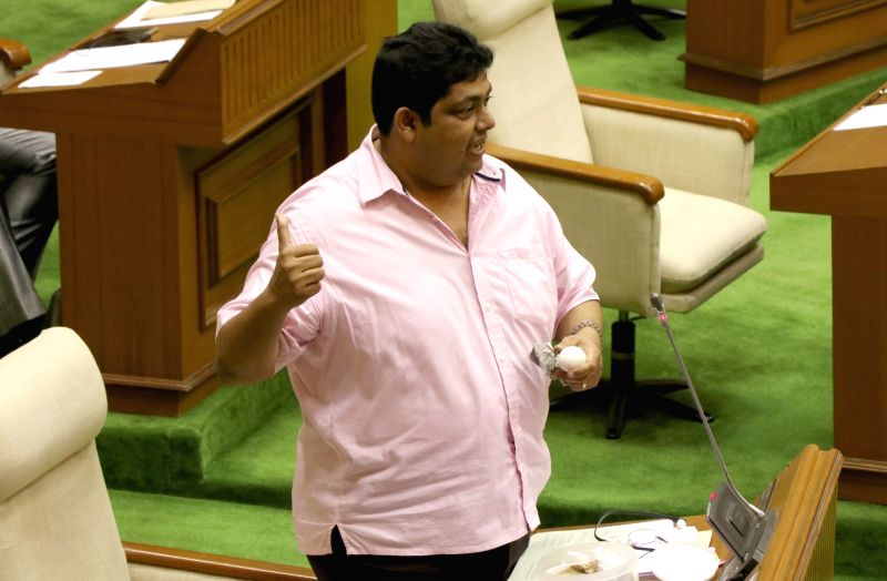 "Congress legislator Aleixo Reginaldo holds an ""artificial"" egg in Goa Assembly in Porvorim, Goa on July 31, 2018. The legislator alleged that eggs made of plastic were being sold ... - Manohar Parrikar"