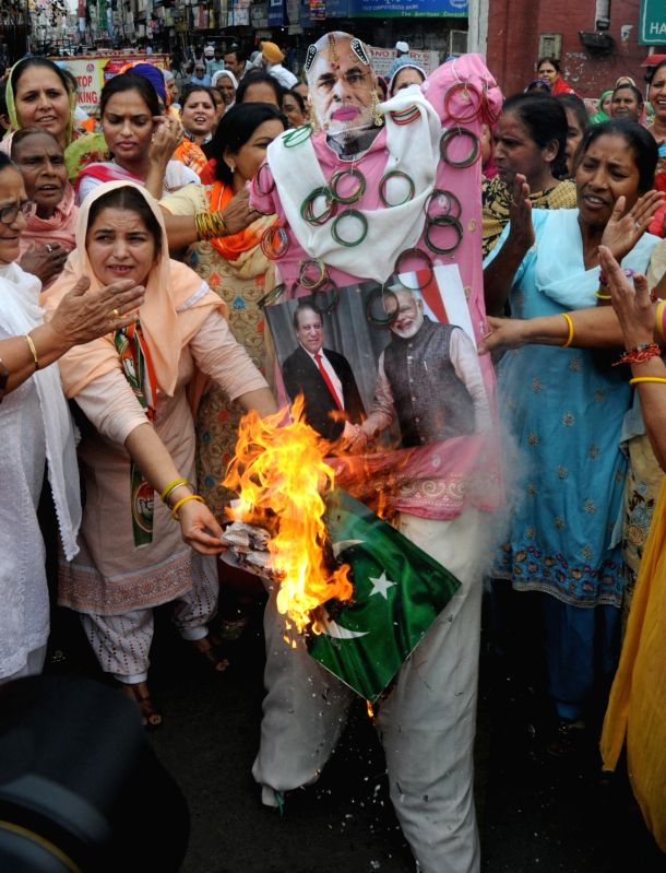 Congress Mahila Morcha workers burn an effigy with pictures of Prime Minister Narendra Modi and his Pakistani counterpart Nawaz Sharif during a demonstration after an Army soldier and a BSF ... - Narendra Modi