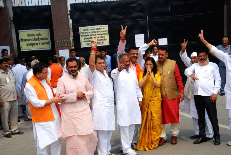 Congress MLA Rekha Arya with BJP MLAs showing victory sign outside the assembly in Dehradun on May 10, 2016. - Rekha