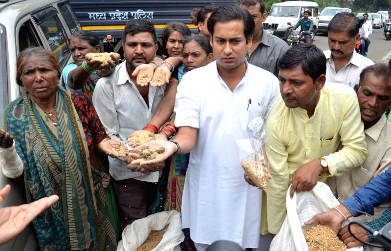 Congress MLAs protest outside the Madhya Pradesh Vidhan Sabha after mud and stones found in relief material during the ongoing flood situation; in Bhopal on July 20, 2016.