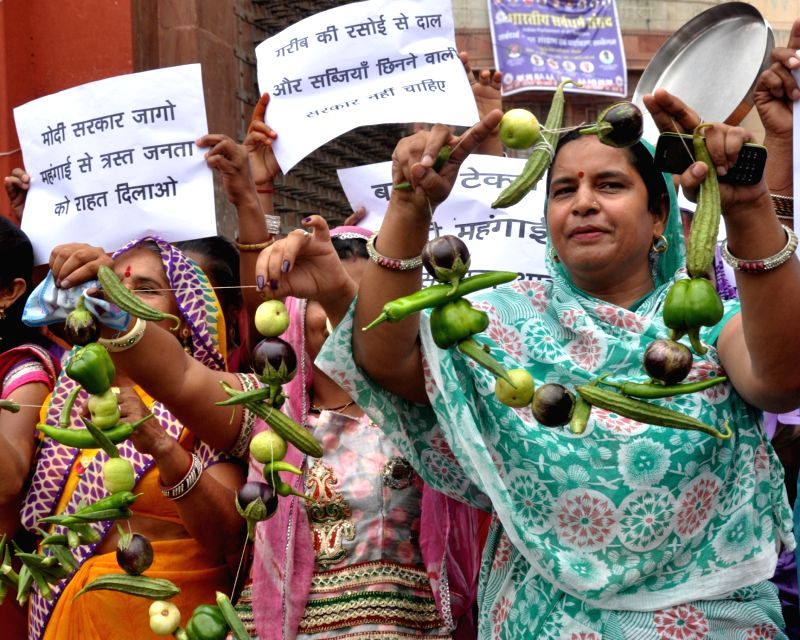 Congress women wing stage a demonstration over price rise of vegetables in Bikaner on July 30, 2016.