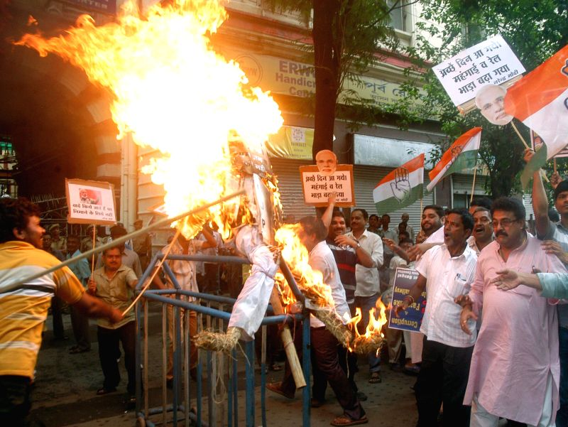 Congress workers burn effigy of Prime Minister Narendra Modi as they demonstrate against rail tariff hike in Kolkata on June 30, 2014. - Narendra Modi