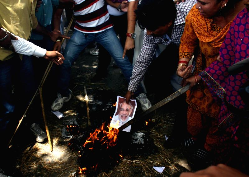 Congress workers burn pictures of Prime Minister Narendra Modi during 'Rail Roko Andolan' organised to protest against rail tariff hike in Bhopal on June 22, 2014. - Narendra Modi