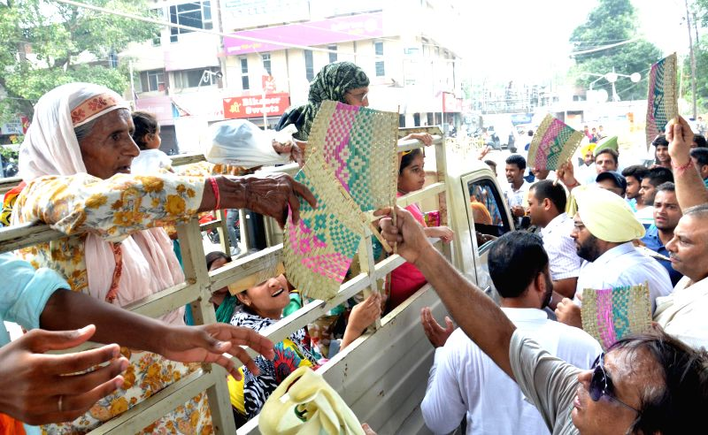 Congress workers distribute fans to public as they demonstrate against power shortage in Amritsar on July 15, 2014.