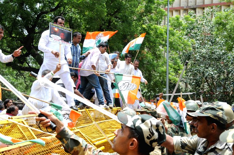 Congress workers jump barricades as they demonstrate against hike in prices of fuel and rail tariff in New Delhi on July 7, 2014.