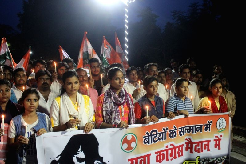 Congress workers participate in a candle light march organised to condemn Deoria shelter home rapes in Lucknow, on Aug 7, 2018.