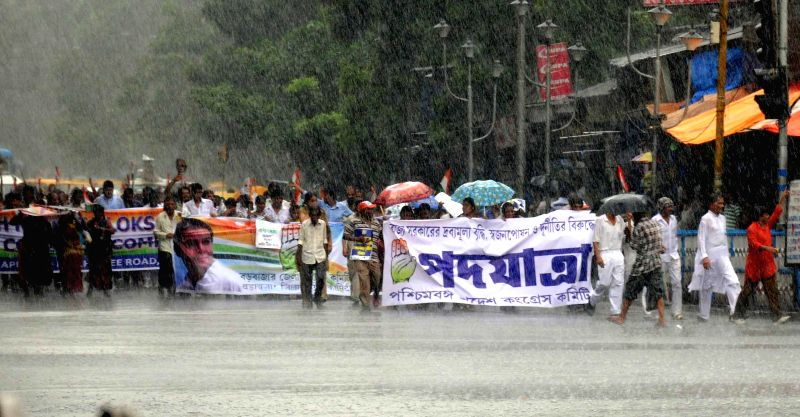 Congress workers participate in a protest rally against West Bengal government and Central government amidst rains in Kolkata on June 25, 2014.