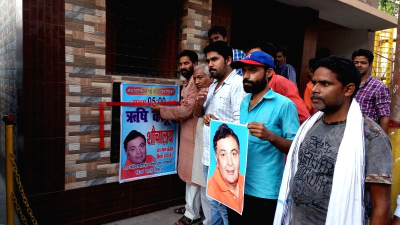 Congress workers paste pictures of actor Rishi Kapoor at a public toilet apparently as a retort to the actor's recent rant over the naming of many public institutions after Nehru-Gandhi ... - Rishi Kapoor and Nehru-Gandhi
