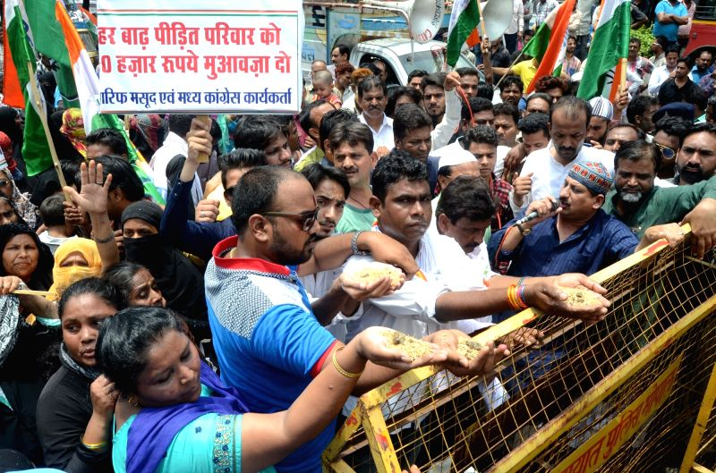 Congress workers stage a demonstration after mud and stones found in relief material during the ongoing flood situation; in Bhopal on July 21, 2016.