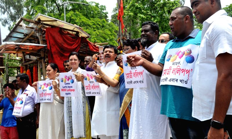 Congress workers stage a protest against the BJP led Union Government holding lollipop in Guwahati on May 26, 2017.