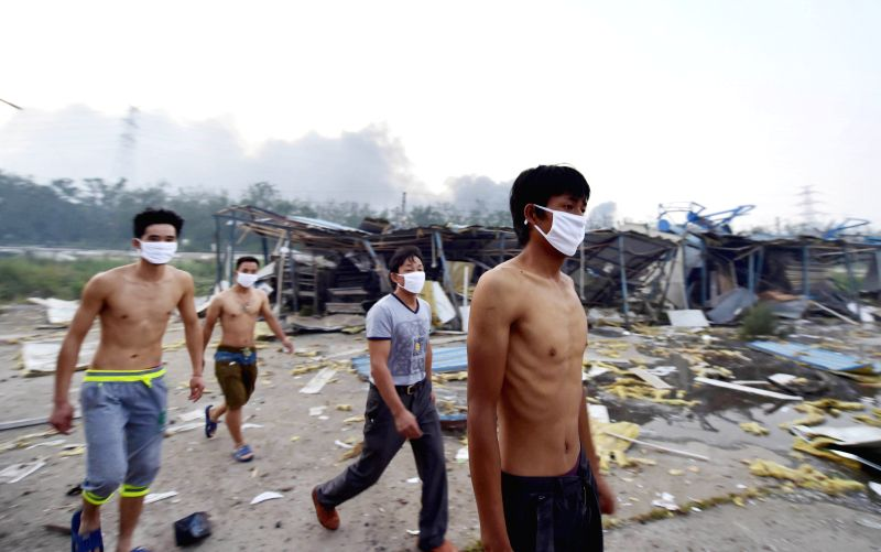 Construction workers return to damaged shanties to search for belongs near the explosion site in the Binhai New Area in north China's Tianjin Municipality, Aug. 13, ...