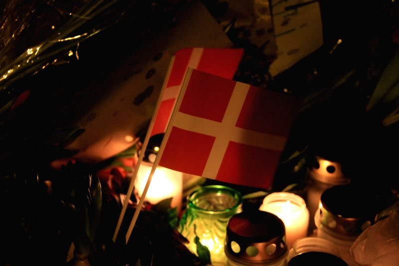 National flags, candles and flowers are seen during a memorial vigil for those killed by a gunman at the weekend in Copenhagen, Denmark, on Feb. 16, 2015. Tens ..