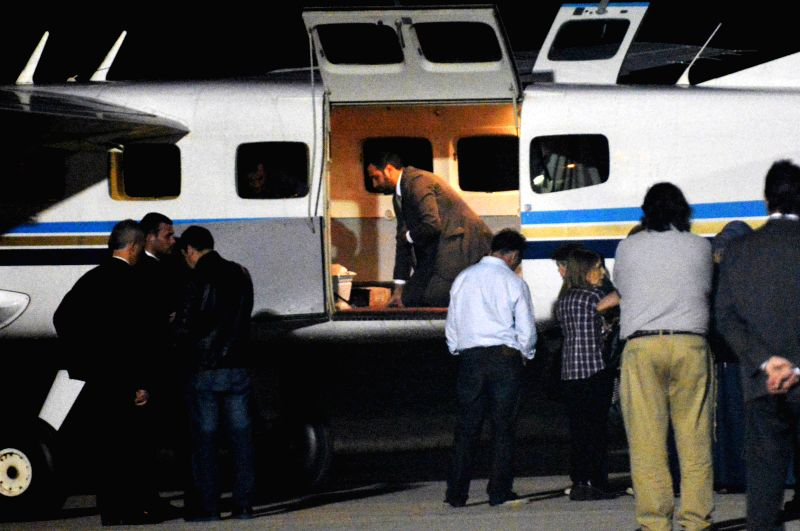 People stand around the plane that will carry the remains of Emanuel Bergoglio's wife and children to the city of Buenos Aires, in Cordoba, Argentina, on Aug. 19, ..