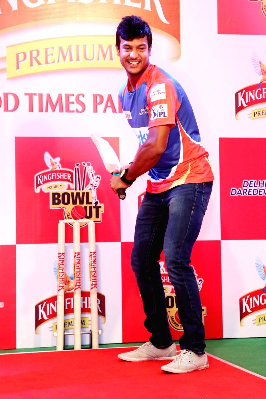 Cricketer Ross Taylor with a child during Kingfisher Bowl Out held at a shopping mall in Gurgaon on May 5, 2014.
