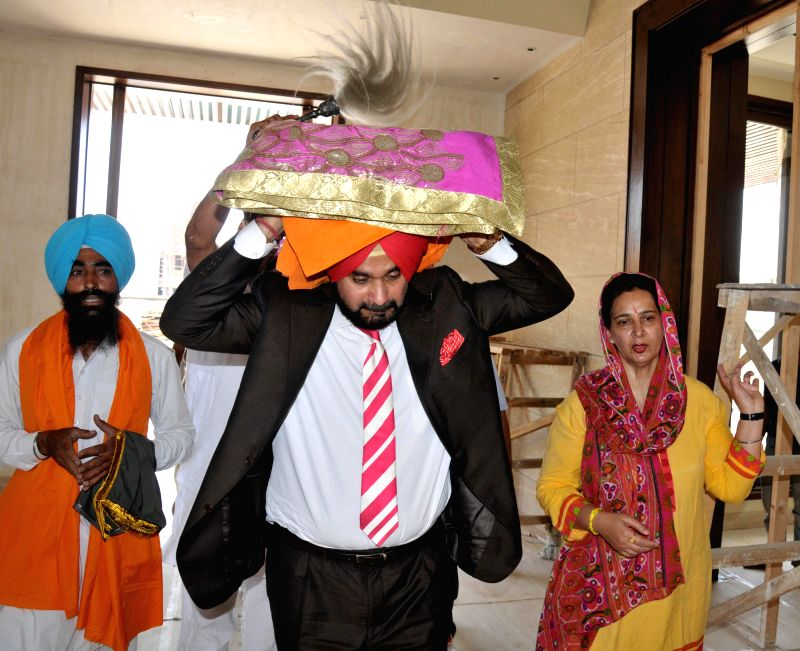 Cricketer-turned-politician Navjot Singh Sidhu carries a swaroop of Sri Guru Granth Sahib on his head to install it in his house, in Amritsar on May 1, 2014.