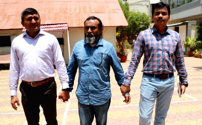 Crime branch officials take away Shoheb Potrinical, an accused in 2008 Ahmedabad serial bomb blast case in Ahmedabad on May 24, 2017.