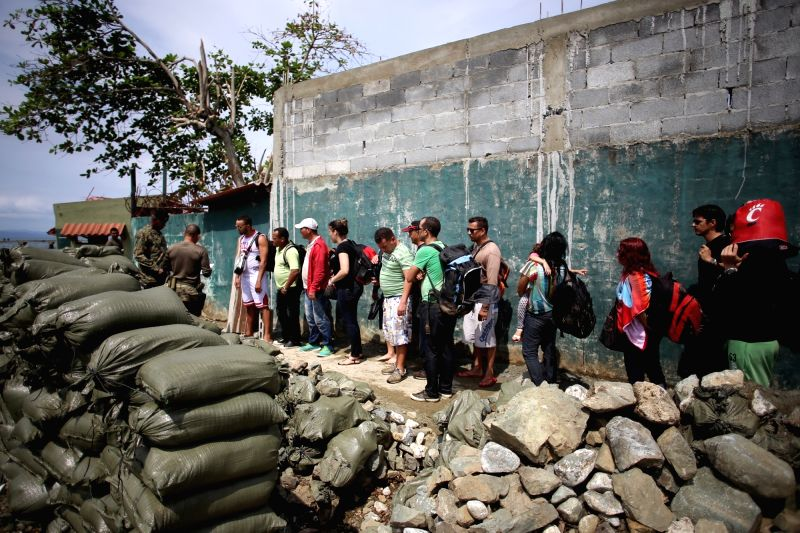 Cuban migrants are reviewed by the National Borders Service in the Puerto Obaldia town, in the indigenous region of Guna Yala, Panama, on Nov. 25, 2015. ...