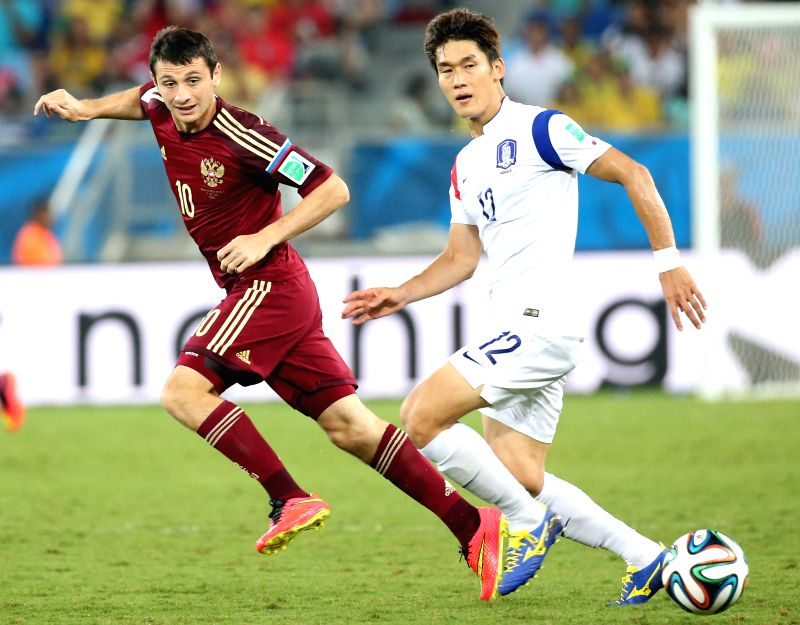 Russia's Alan Dzagoev (L) vies with Korea Republic's Lee Yong during a Group H match between Russia and Korea Republic of 2014 FIFA World Cup at the Arena Pantanal ..