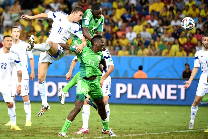 Nigeria's Kenneth Omeruo (front) vies with Bosnia and Herzegovina's Edin Dzeko (up) during a Group F match between Nigeria and Bosnia and Herzegovina of 2014 FIFA ...