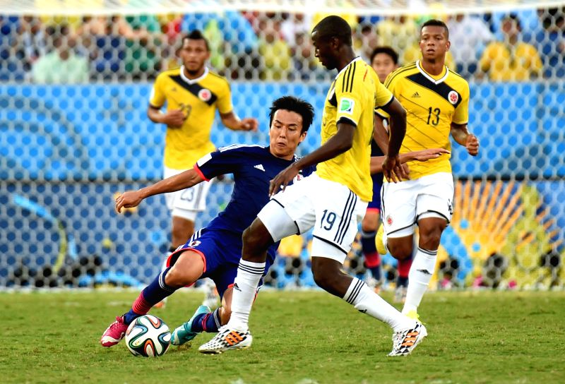 (Japan's Makoto Hasebe vies with Colombia's Adrian Ramos during a Group C match between Japan and Colombia of 2014 FIFA World Cup at the Arena Pantanal Stadium in ...