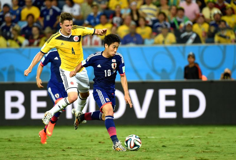 (Japan's Shinji Kagawa vies with Colombia's Santiago Arias during a Group C match between Japan and Colombia of 2014 FIFA World Cup at the Arena Pantanal Stadium in .