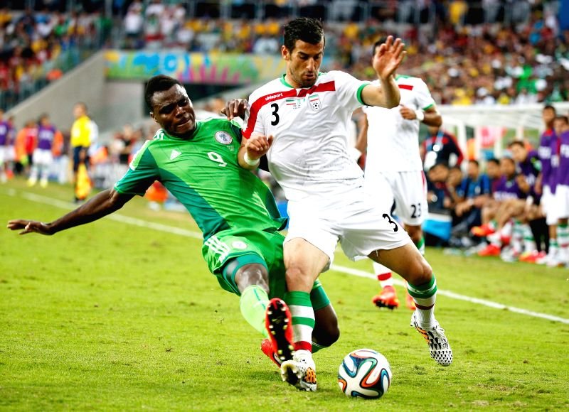 Iran's Ehsan Hajsafi (R) vies with Nigeria's Emmanuel Emenike during a Group F match between Iran and Nigeria of 2014 FIFA World Cup at the Arena da Baixada ...