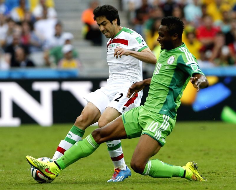 Iran's Khosro Heydari (L) vies with Nigeria's Mikel Obi during a Group F match between Iran and Nigeria of 2014 FIFA World Cup at the Arena da Baixada Stadium in ..