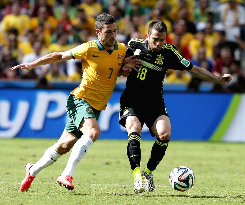 Spain's Jordi Alba (R) vies with Australia's Matthew Leckie during a Group B match between Australia and Spain of 2014 FIFA World Cup at the Arena da Baixada Stadium .