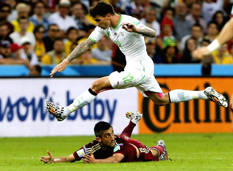 Algeria's Carl Medjani vies with Russia's Alexander Samedov during a Group H match between Algeria and Russia of 2014 FIFA World Cup at the Arena da Baixada ...