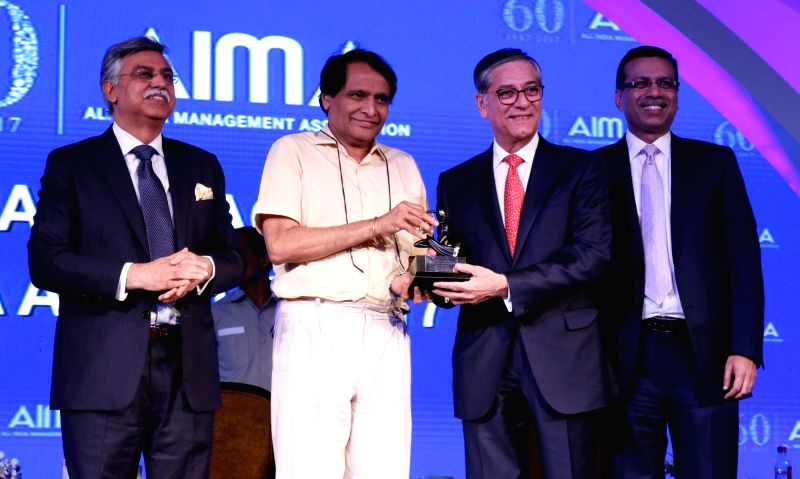 Dabur Group chairman Anand Burman receives Outstanding Institution Builder from Union Railway Minister Suresh Prabhu at the AIMA Awards ceremony in New Delhi, on April 27, 2017. - Suresh Prabhu