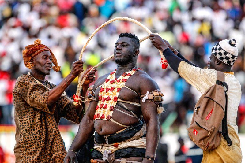 "Balla Gaye 2 (C) performs mysterious ritual before the Senegalese traditional wrestling match ""Le Choc"" at Demba Diop Stadium, Dakar, capital of Senegal, ..."