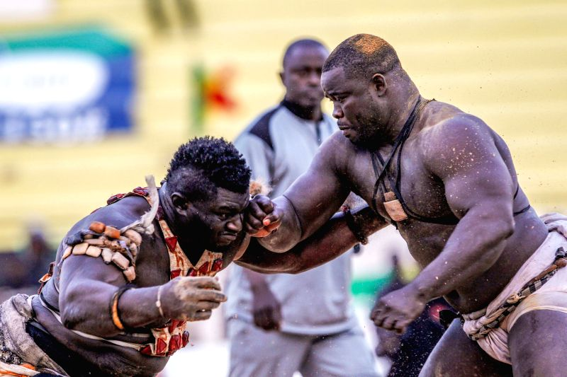 """Balla Gaye 2 (L) competes with Eumeu Sene during the Senegalese traditional wrestling match """"Le Choc"""" at Demba Diop Stadium, Dakar, capital of Senegal, ..."""