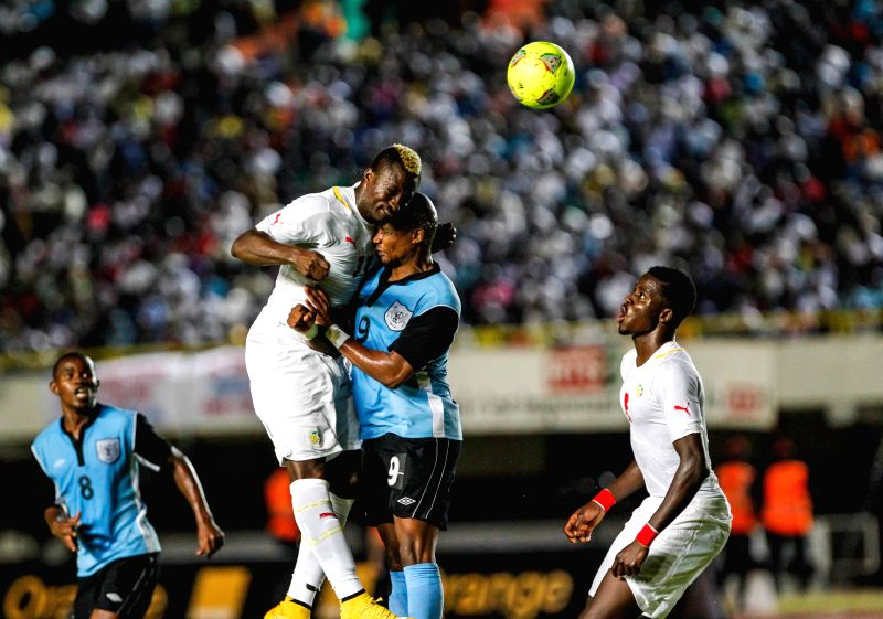 Senegal's Dame Ndoye (2nd, L) heads the ball with Botswana's Jerome Ramatlhakwana during the final round of Africa Cup of Nations Morocco 2015 qualifying match in Dakar, Senegal, Nov. 19, ...