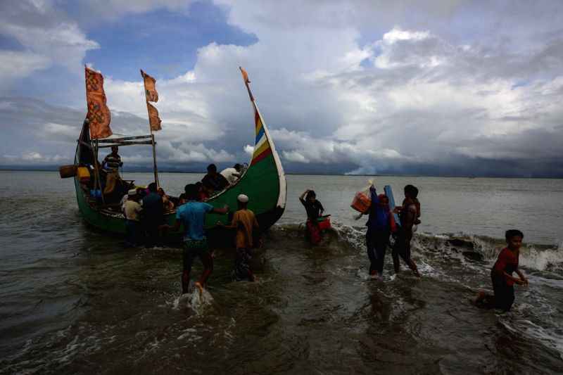 Dakhinpara: Rohingya refugees arrive at Shah Porir Dwip in Dakhinpara ofBangladesh from Rasidong in Myanmar, on Sept 13, 2017. (Photo: bdnews24/IANS)