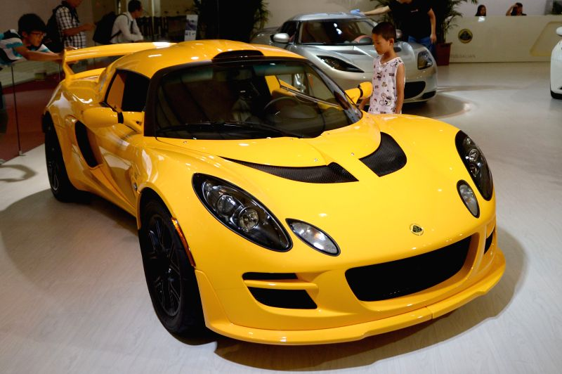 A child watches a motorcar at the 19th Dalian International Automotive Exhibition in Dalian, northeast China's Liaoning Province, Aug. 27, 2014. The 5-day ...