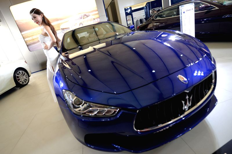 A model poses for photo beside a motorcar at the 19th Dalian International Automotive Exhibition in Dalian, northeast China's Liaoning Province, Aug. 27, 2014. The ..