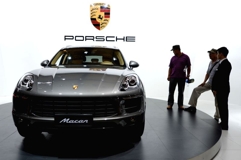 Visitors watch a Porsche motorcar at the 19th Dalian International Automotive Exhibition in Dalian, northeast China's Liaoning Province, Aug. 27, 2014. The 5-day ...
