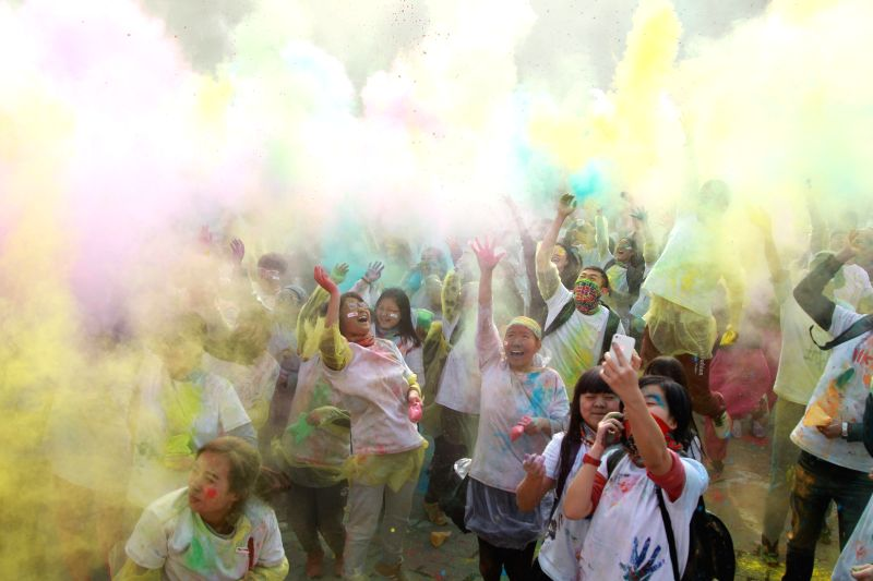 Dalian (China): Runners throw colorful powder in the air while taking part in a color run in Dalian, northeast China's Liaoning Province, Nov. 29, 2014. Over 2,000 runners participated in the 5-km ...