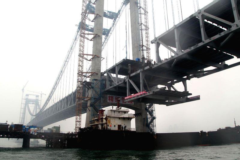 Workers install the last truss girder of Xinghaiwan Bridge in Dalian, northeast China's Liaoning Province, Jan. 5, 2015. The closure of the 6-kilometer-long bridge ...