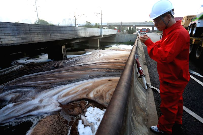 A firefighter checks the crude oil spills at the exit of the urban sewage pipeline network after a crude oil spill from a pipeline of PetroChina, the country's ...