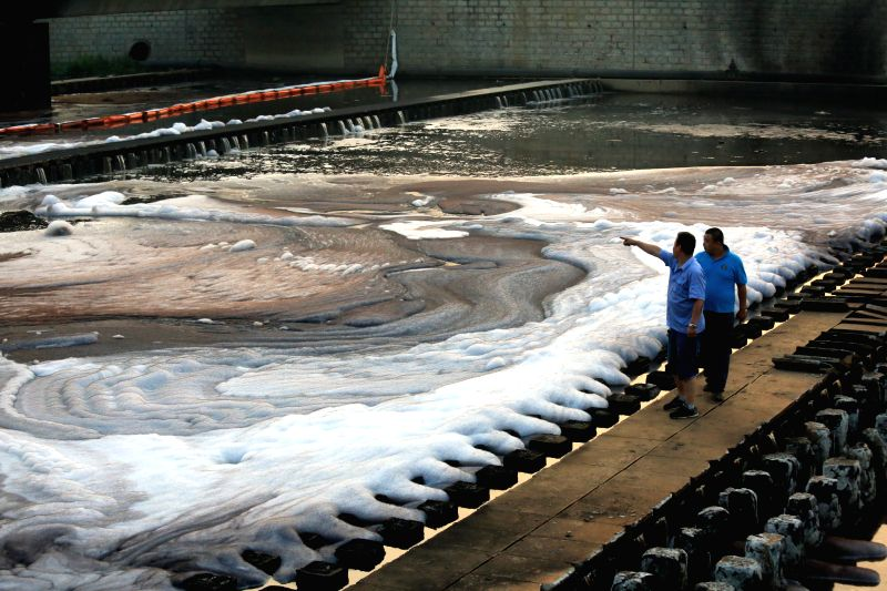 Working staff check the crude oil spills at the exit of the urban sewage pipeline network after a crude oil spill from a pipeline of PetroChina, the country's largest