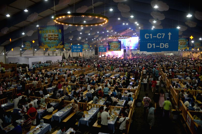 Citizens and tourists drink beer during the 16th China International Beer Festival in Dalian, northeast China's Liaoning Province, July 24, 2014. The 12-day beer ...