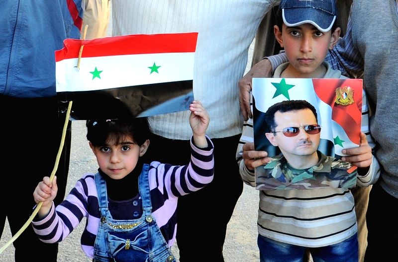 DAMASCUS, April 19, 2017 - Syrians hold a Syrian flag and a portrait of President Bashar al-Assad in the town of Zabadani, western countryside of Damascus, capital of Syria, following the evacuation ...