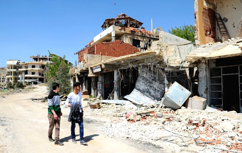 DAMASCUS, April 25, 2017 - Syrian men walk past destroyed buildings in the mountainous city of Zabadani, in the western countryside of Damascus, capital of Syria, on April 25, 2017. The towns of ...