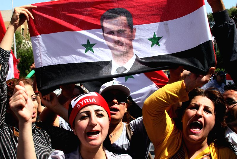 Syrians take part in a a rally to show support for President Bashar al-Assad in Damascus, Syria, April 28, 2014. Syria's President Bashar al-Assad has registered .