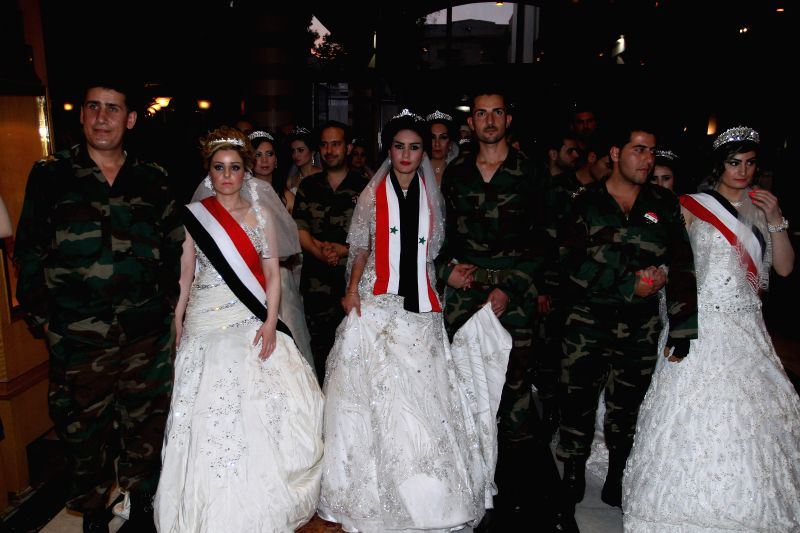 Syrian couples take part in their mass wedding held at the Dama Rose hotel in Damascus, Syria, April 29, 2014. Twenty bridegrooms wearing their military uniforms .