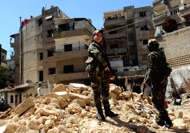 Two female snipers patrol in Daraya suburb of the capital Damascus, Syria, on April 5, 2015. The snipers are members of the female force in Syrian Republican ...